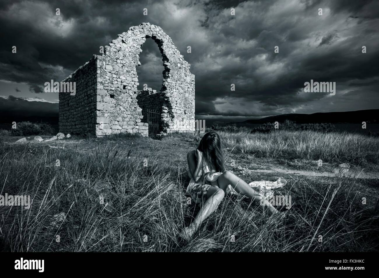 Young woman before abandoned house Black & White retro sitting seated apparently almost evidently - Stock Image