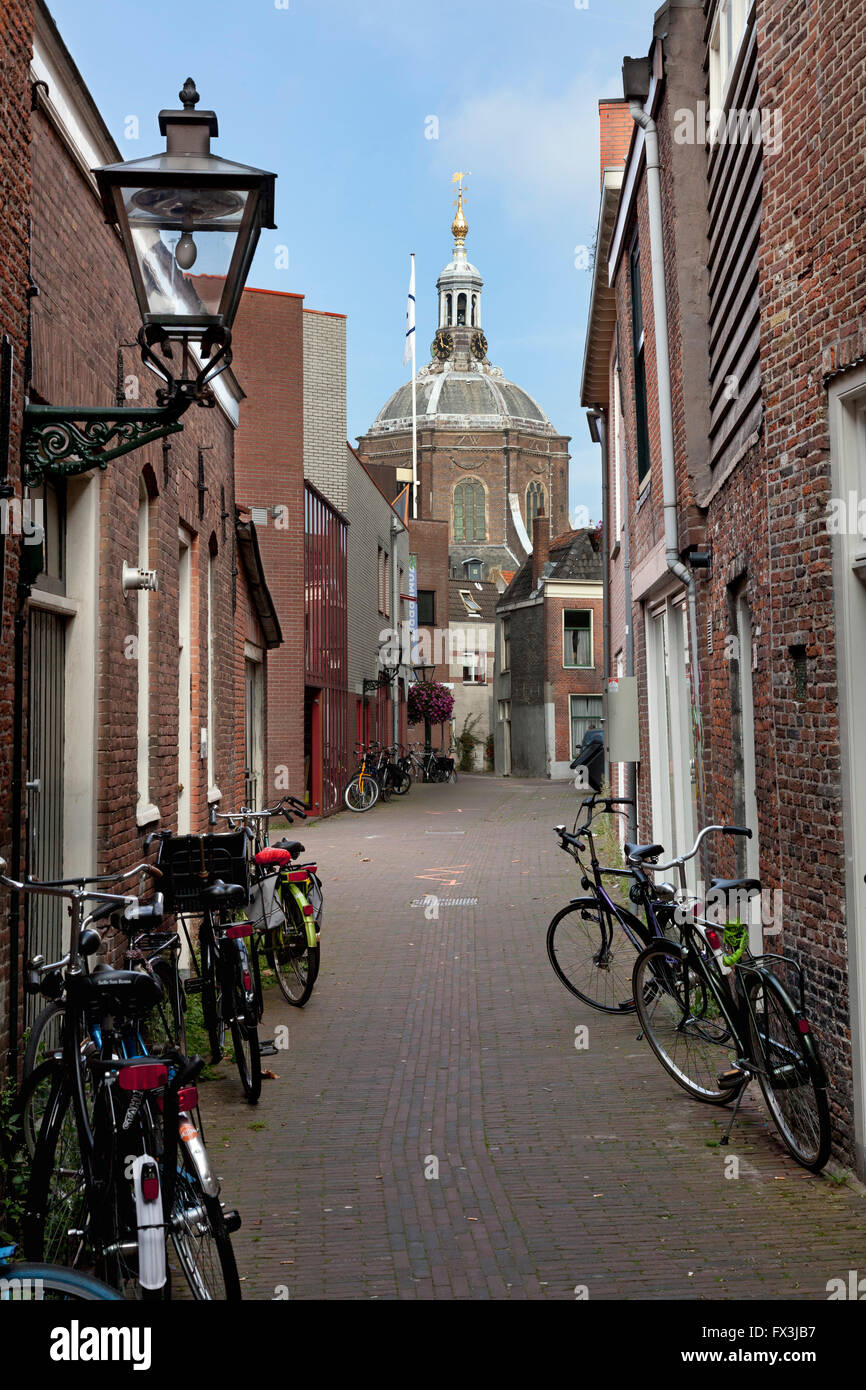 Alley with bikes in the city of Leiden with a view on the Marekerk - Stock Image