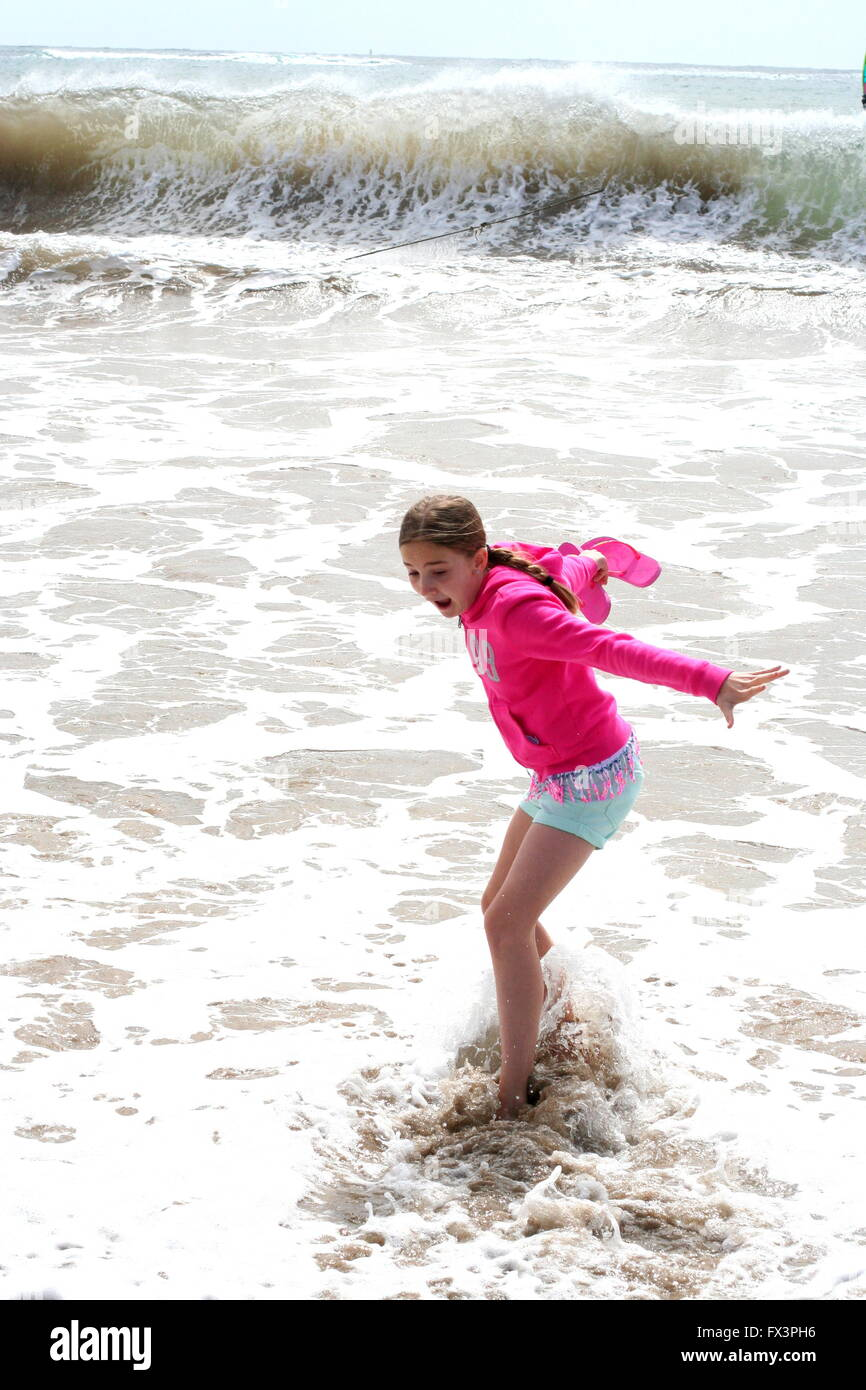 Girl child kidriding the wave a beach in Spain with foamy waves, pure joy happiness concept, best life, contentment, - Stock Image