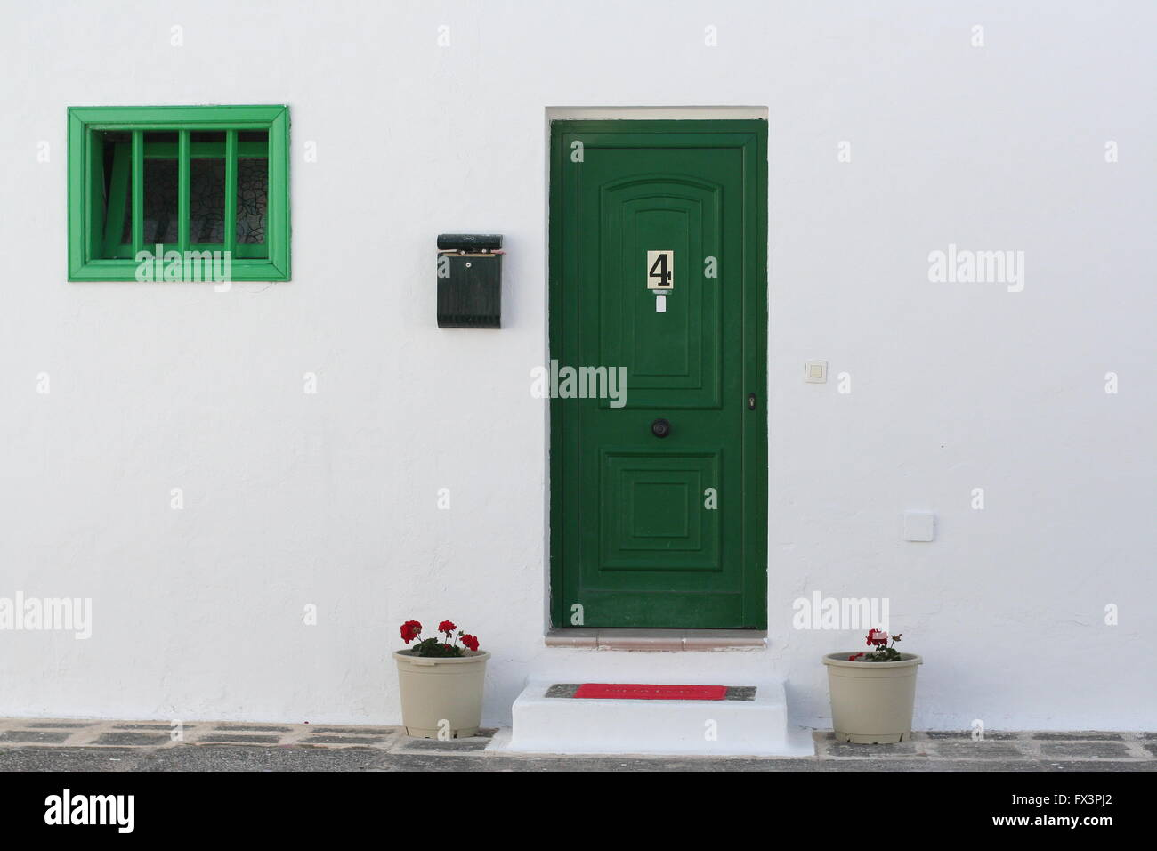 Green front door and clad window, number 4 on a spanish street, Lanzarote Spain, home sweet home concept, holiday - Stock Image