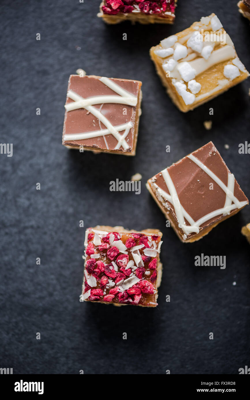 Brownie bites with chocolate and cranberry from above on dark slate - Stock Image