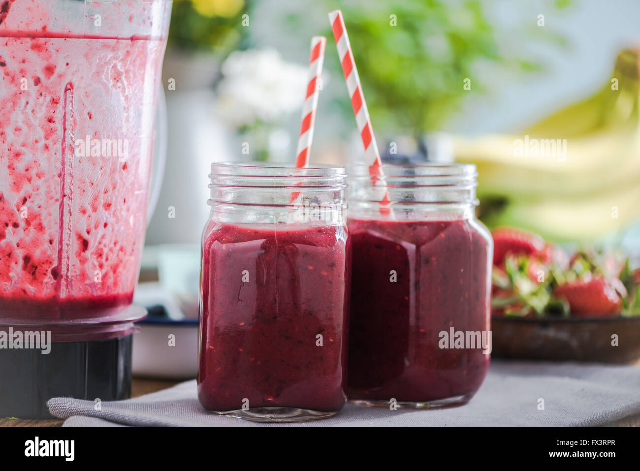 Berry smoothie on wooden table in sunny kitchen, negative space for text. - Stock Image