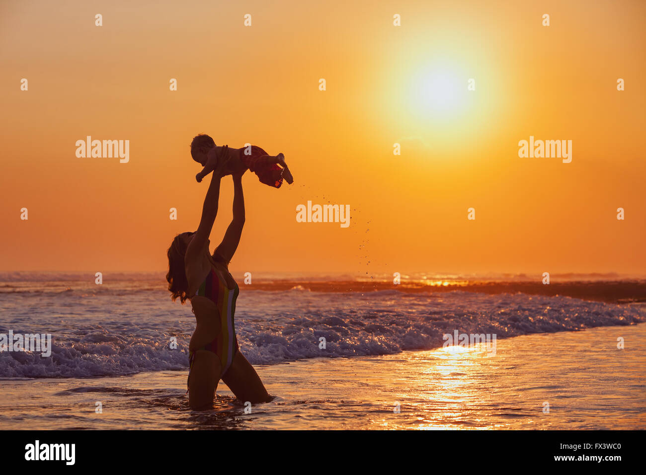 Happy family swimming fun on sea beach - mother tossing up baby son into mid air, catching on sunset sky on sun - Stock Image