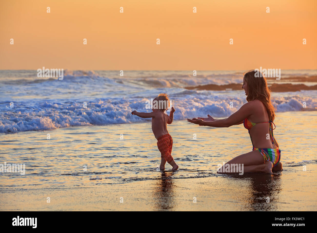 Family swimming fun in sea beach surf Happy mother, baby son first step - toddler run to ocean wave on sunset sky - Stock Image