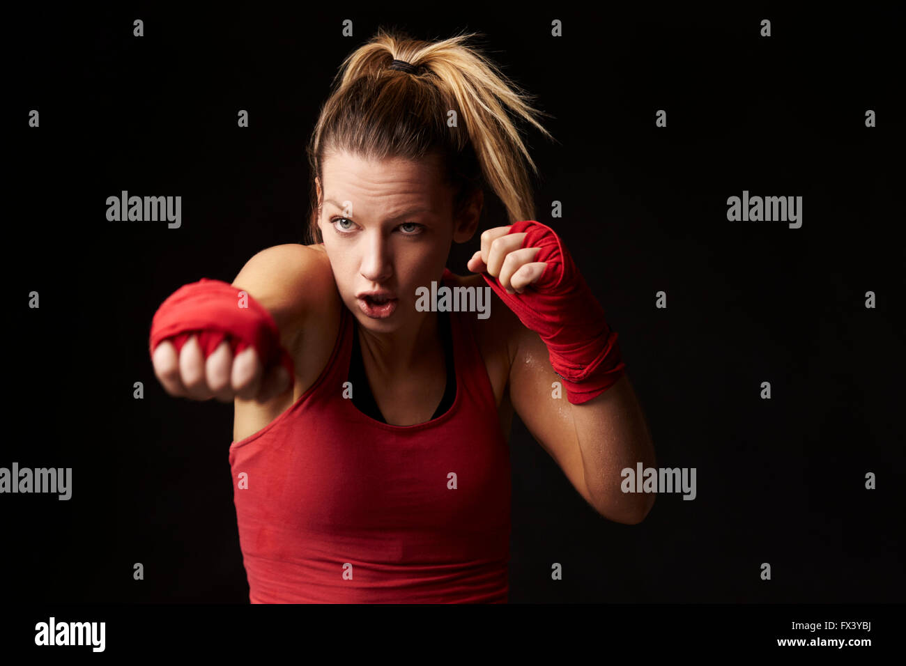 Young blonde woman shadow boxing, throwing a punch - Stock Image