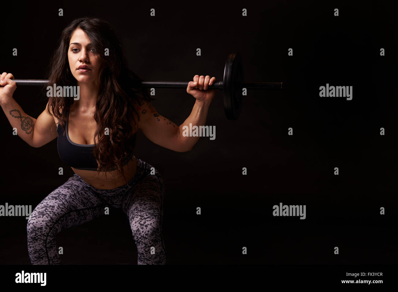 Muscular dark haired woman in half squat with barbell - Stock Image