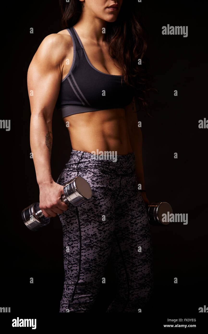 Muscular dark haired woman working out with dumbbells, crop - Stock Image