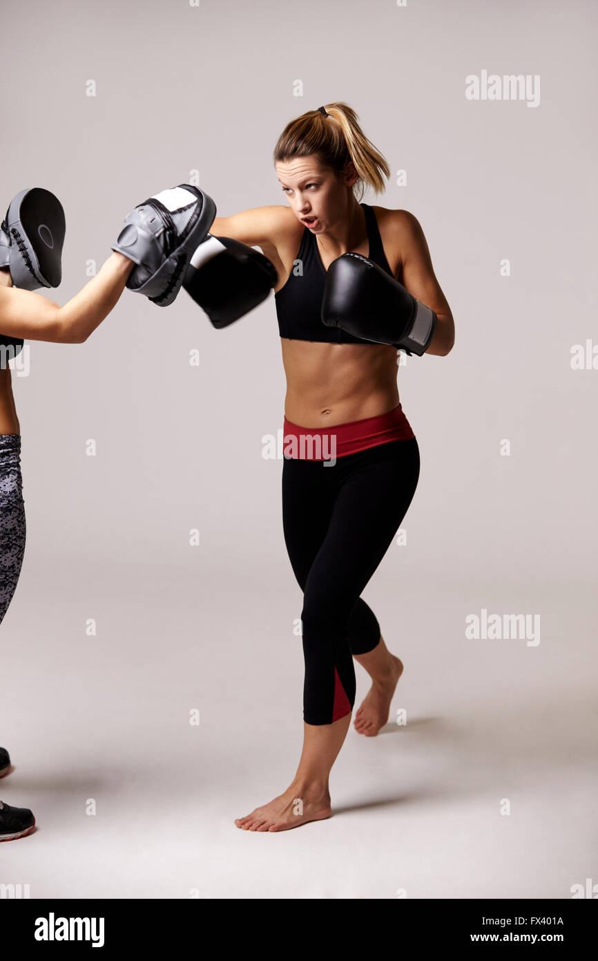 Female boxer practicing with sparring partner, full length - Stock Image