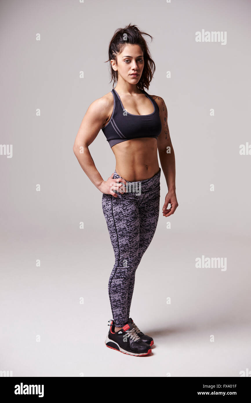 Full length portrait of muscular, dark haired young woman - Stock Image