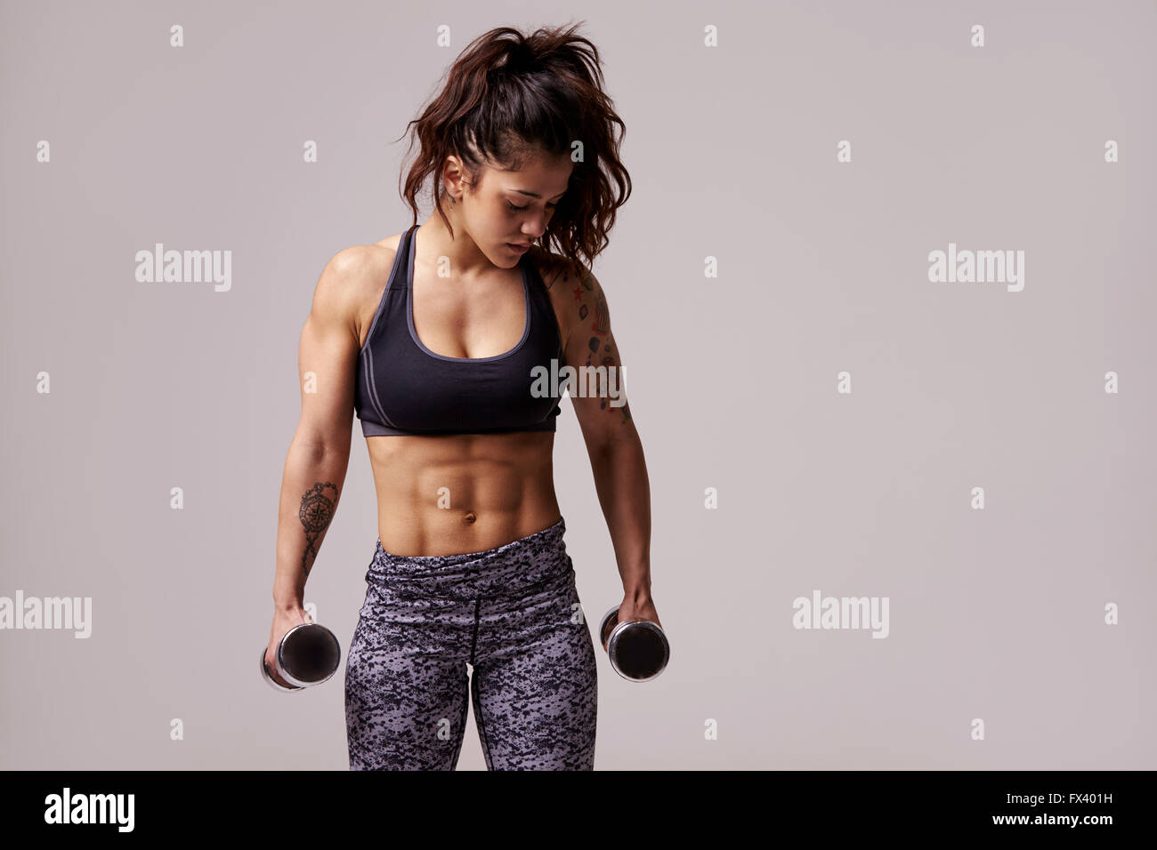 Muscular dark haired young woman working out with dumbbells - Stock Image