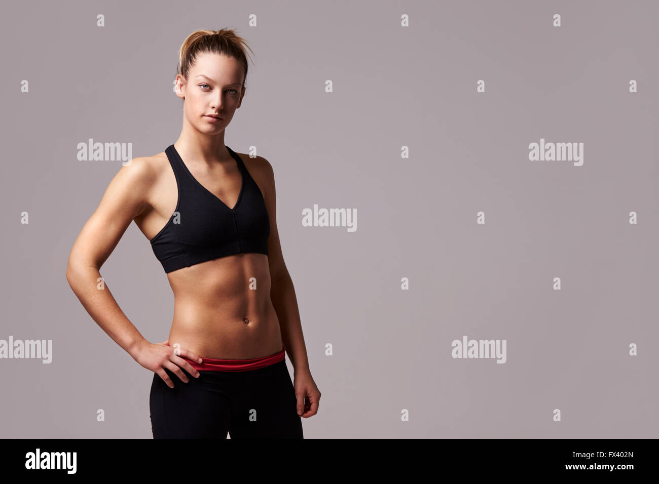 Portrait of athletic woman, hand on hip looking to camera - Stock Image