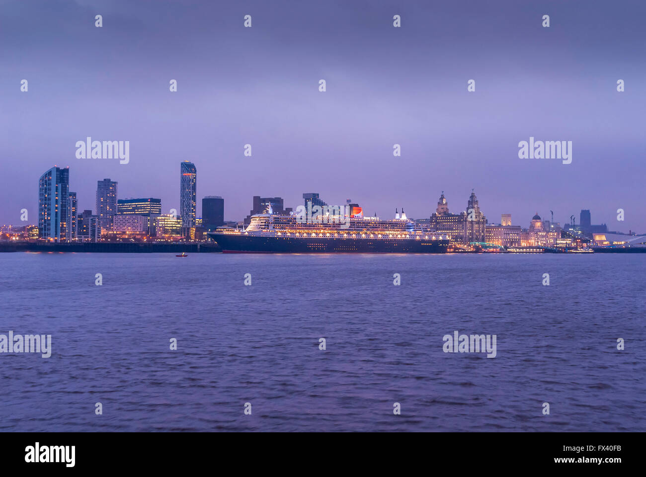 Liverpool waterfront twinkling at in the late evening light with the Cunard liner Queen Mary 2 berthed. - Stock Image