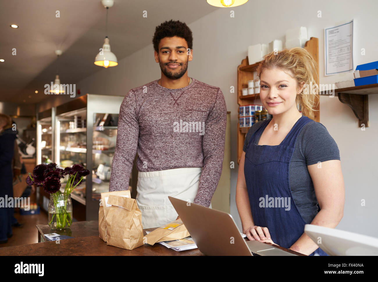 Portrait Of Delicatessen Staff Standing At Checkout - Stock Image