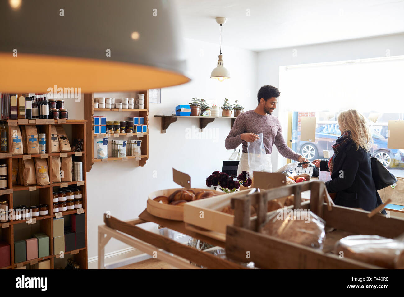Male Sales Assistant Serving Female Customer In Delicatessen Stock Photo