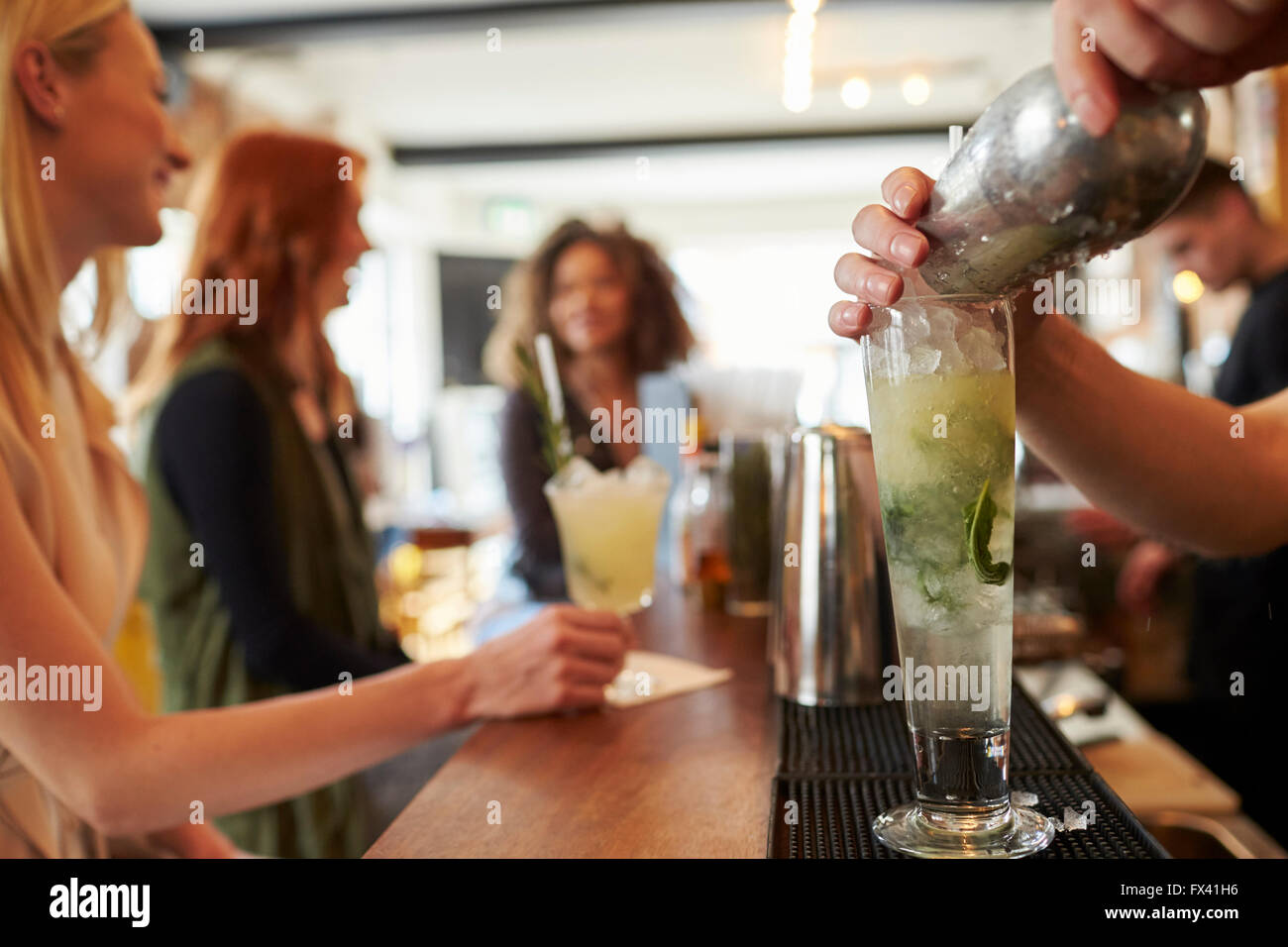 Barman Pouring Mojito Cocktail With Customers In Background - Stock Image