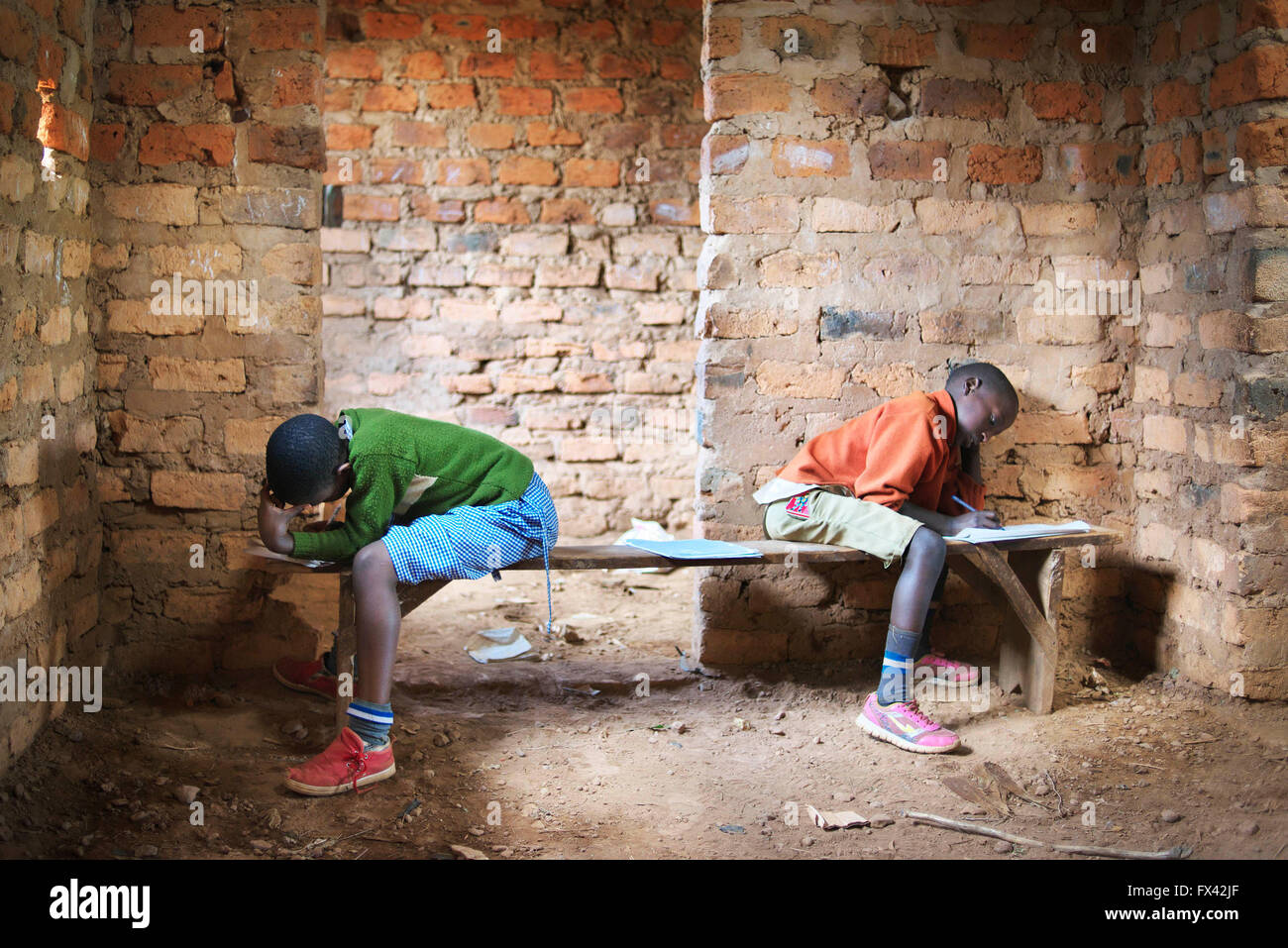 Two brightly dressed school children take exams in a rural school in Uganda, East Africa Stock Photo