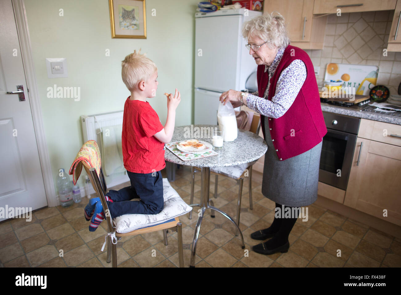 Elderly pensioner (aged 80) caring for her grandsons (aged 2 and 5), at home in Dorset, England, UK - Stock Image