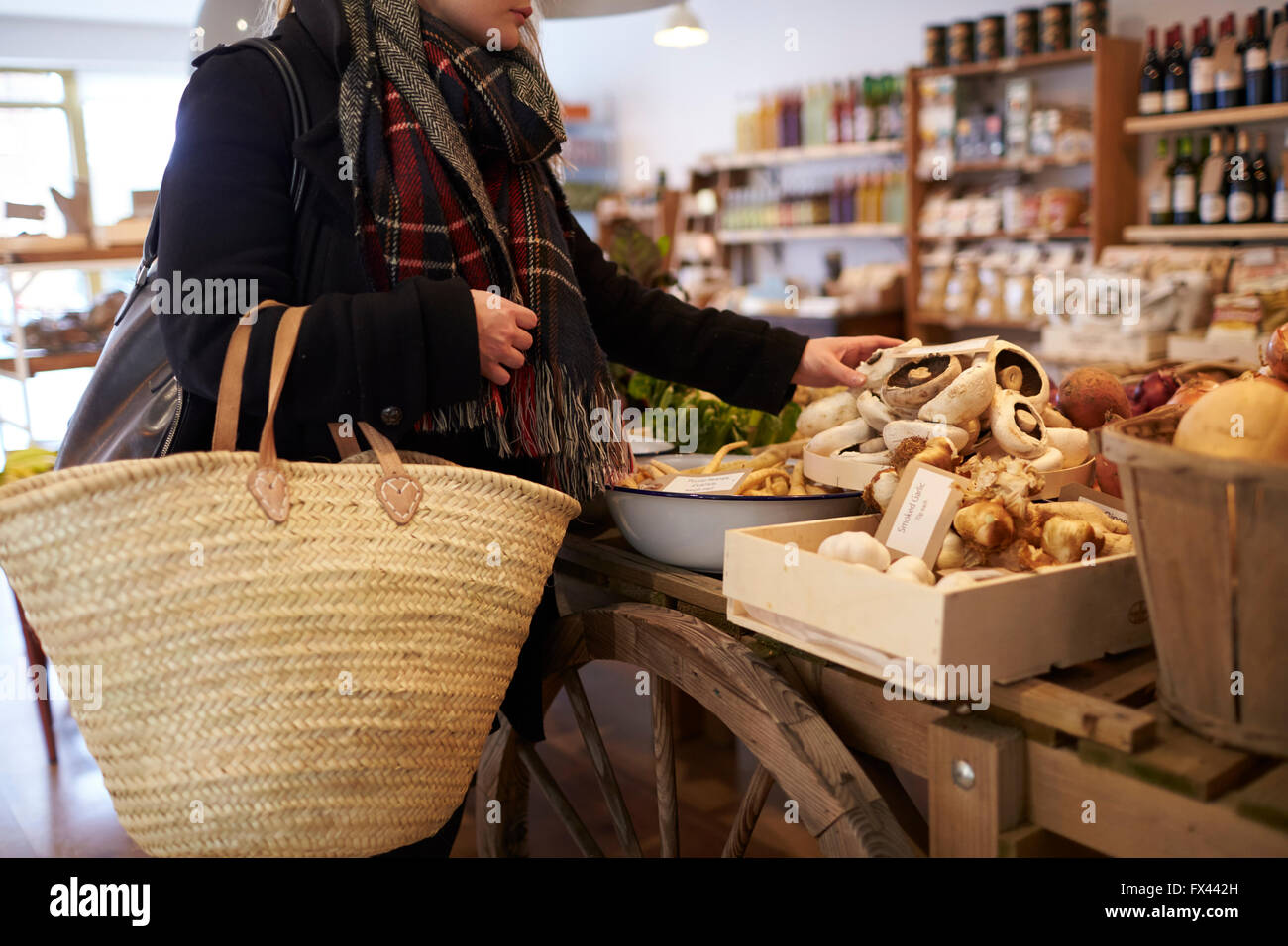 Close Up Of Woman Shopping For Produce In Delicatessen - Stock Image
