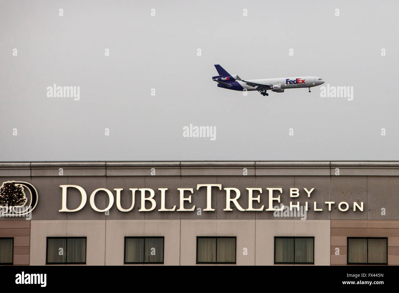 Rosemont, Illinois - A FedEx jet above a DoubleTree Hotel, on final approach to O'Hare Airport. - Stock Image