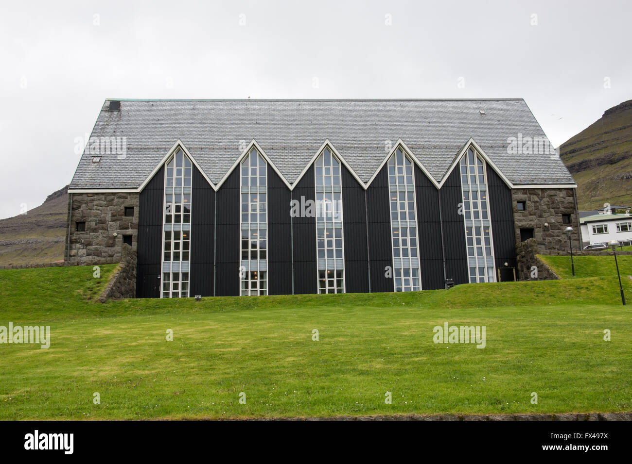 Church in Klaksvik as seen from the outside with landscape and mountain in the background - Stock Image
