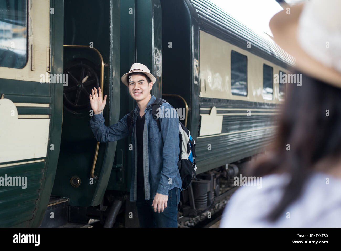 Handsome Young Asian man say goodbye to girlfriend at train station before journey - Stock Image