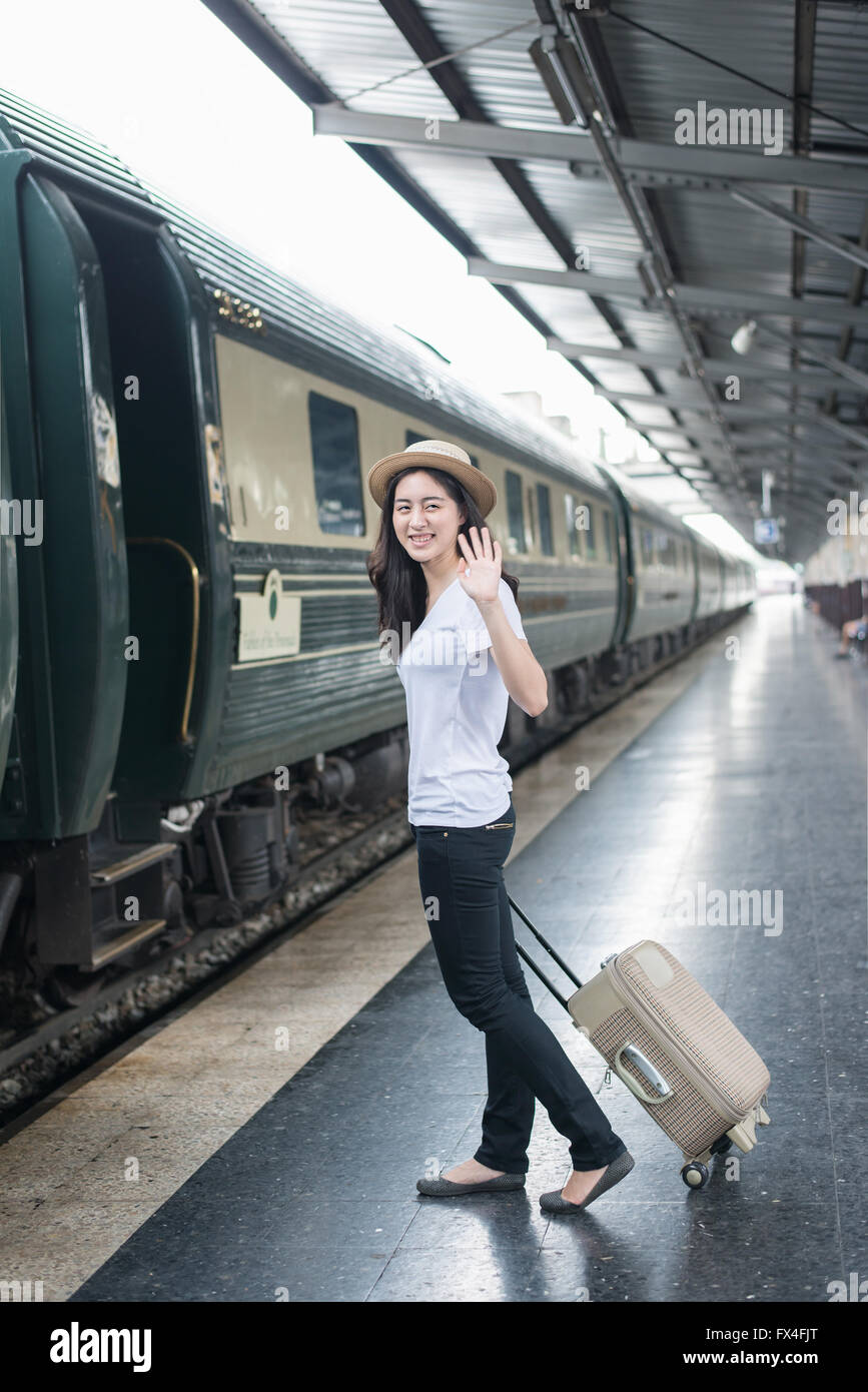 Young Asian woman say goodbye to boyfriend at train station before journey - Stock Image