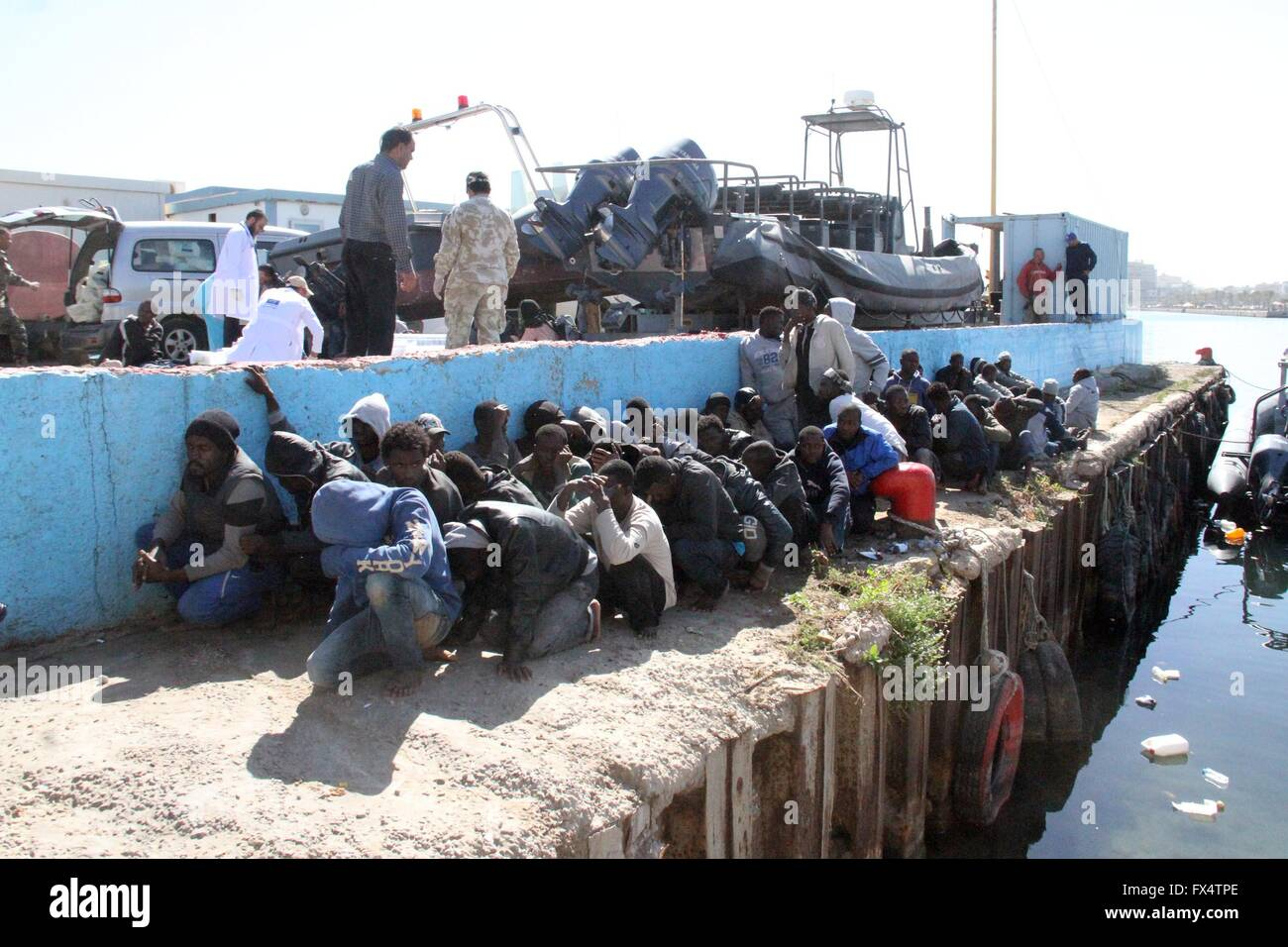 Tripoli. 11th Apr, 2016. Illegal migrants sit on the dock at the Tripoli port after 115 migrants of African origins - Stock Image