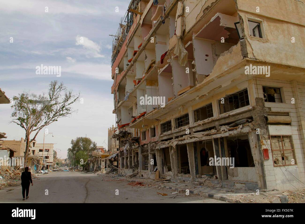 Palmyra, Syria. 11th Apr, 2016. A Syrian civilian walks past a damaged building in Palmyra, central Syria, on April - Stock Image