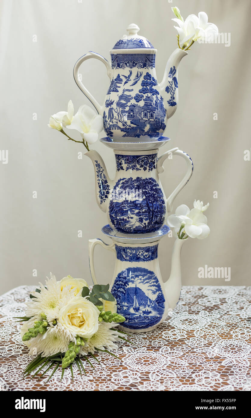 fb08c0faa1b0 Blue and white willow pattern stacked coffee pots on lace cloth for wedding  afternoon tea with roses and bouquet