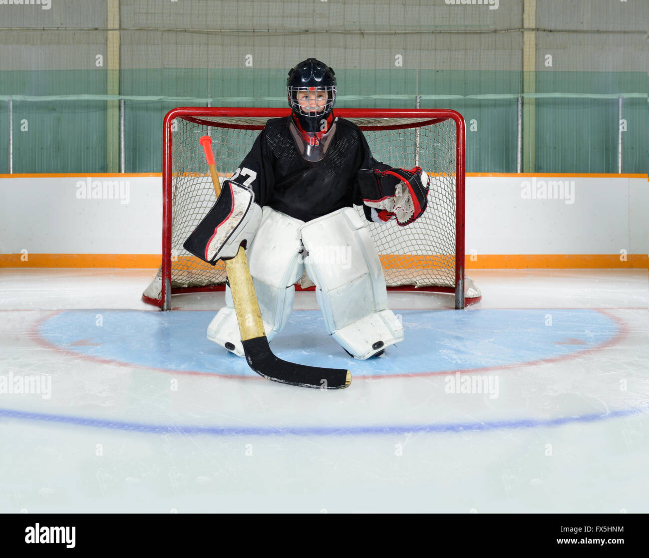 A Young Hockey Goalie Kid Protects his Net from a Goal.  Photographed in the crease of a hockey arena with freshly - Stock Image