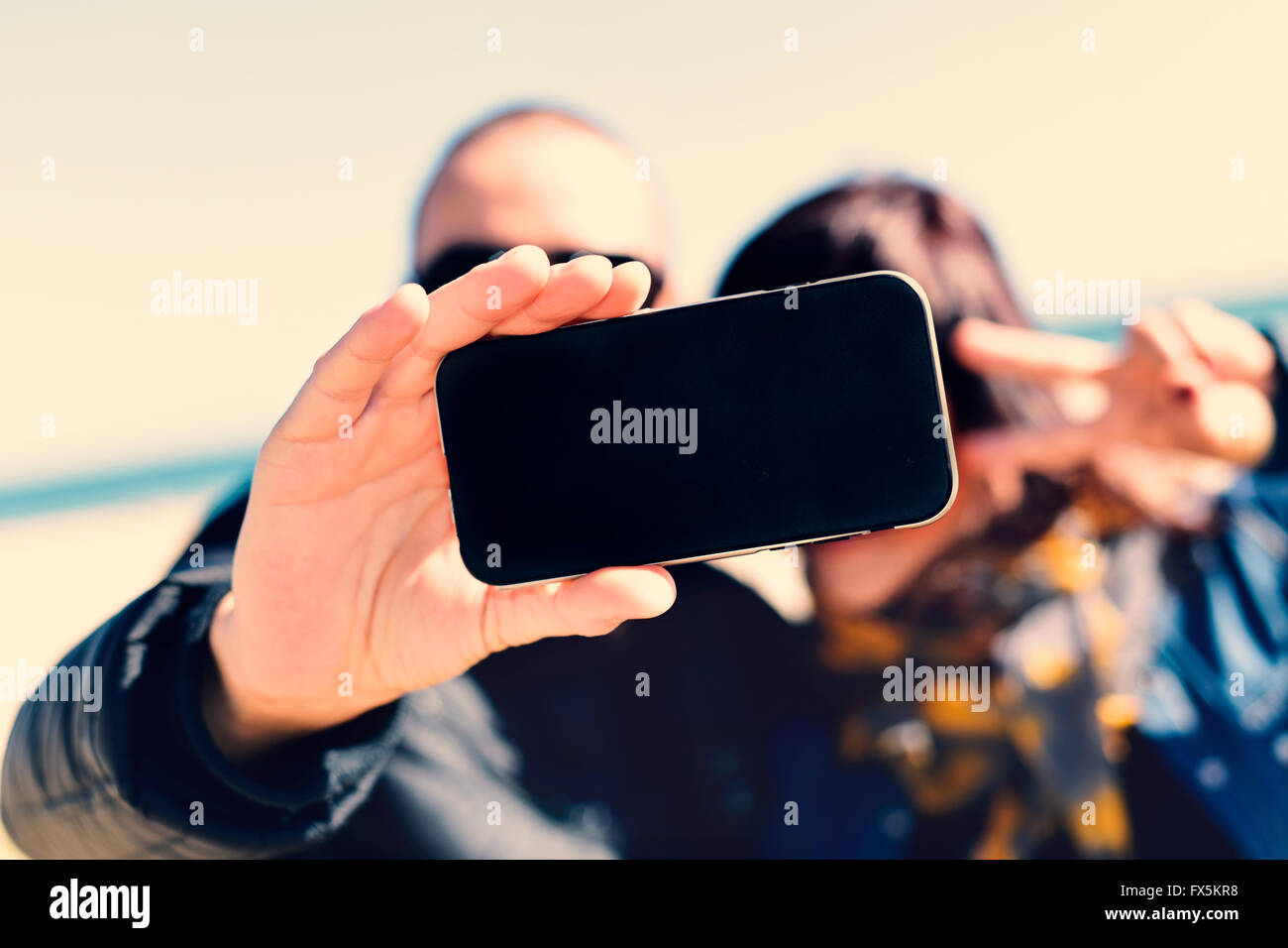 closeup of a young man and a young woman taking a self-portrait with a smartphone while she is doing the victory - Stock Image