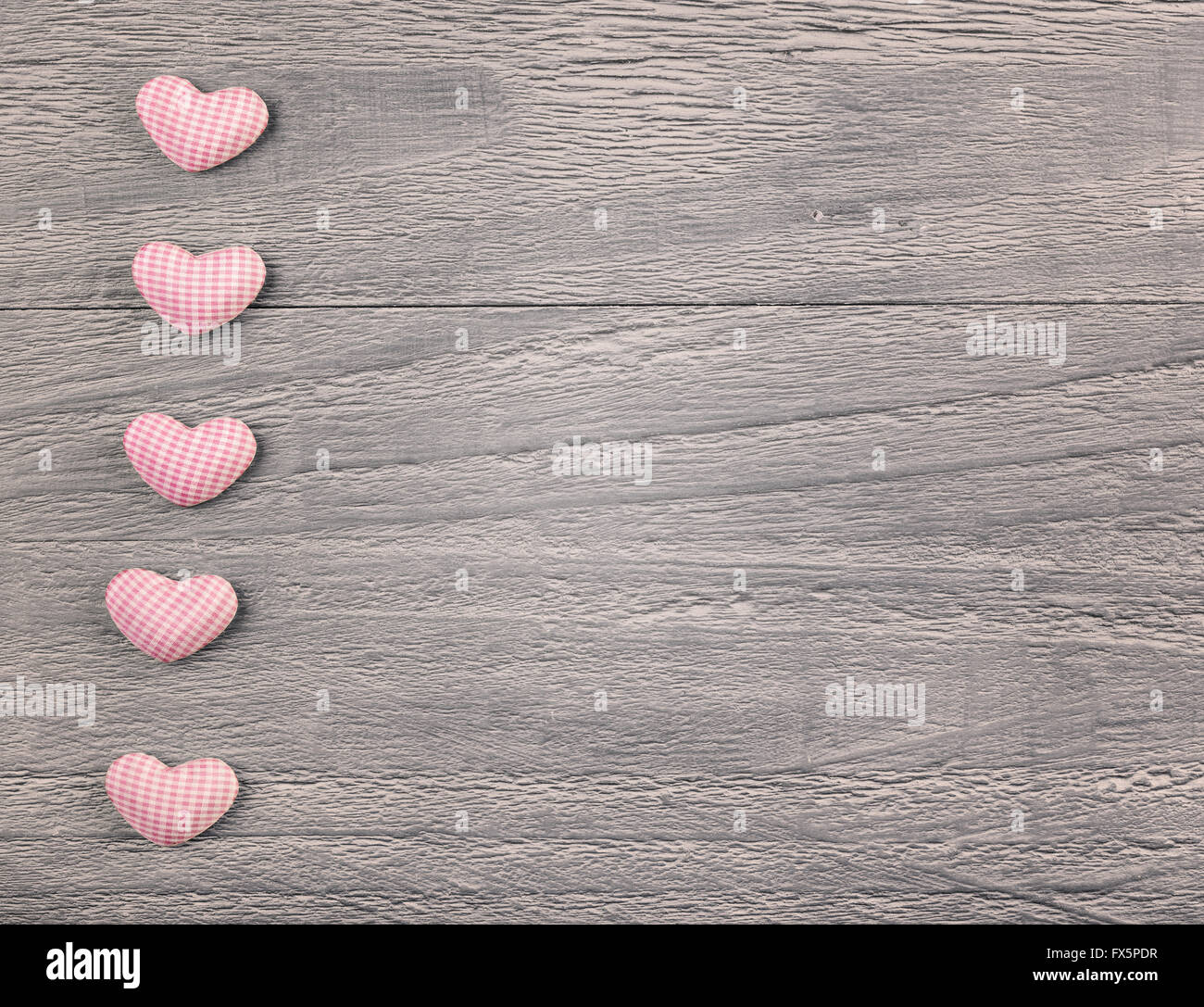 wooden background with gingham hearts toning in vintage style - Stock Image