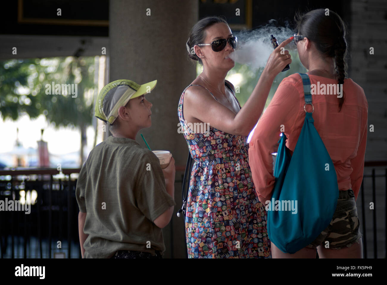 Passive smoking. Mother smoking e cigarette and blowing smoke into child's face. - Stock Image