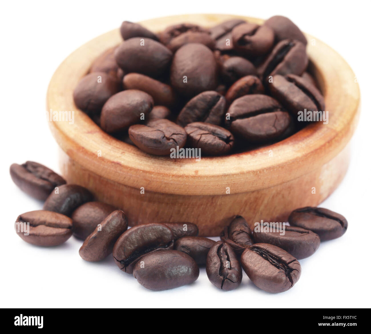 Roasted coffee bean in a wooden bowl over white background - Stock Image