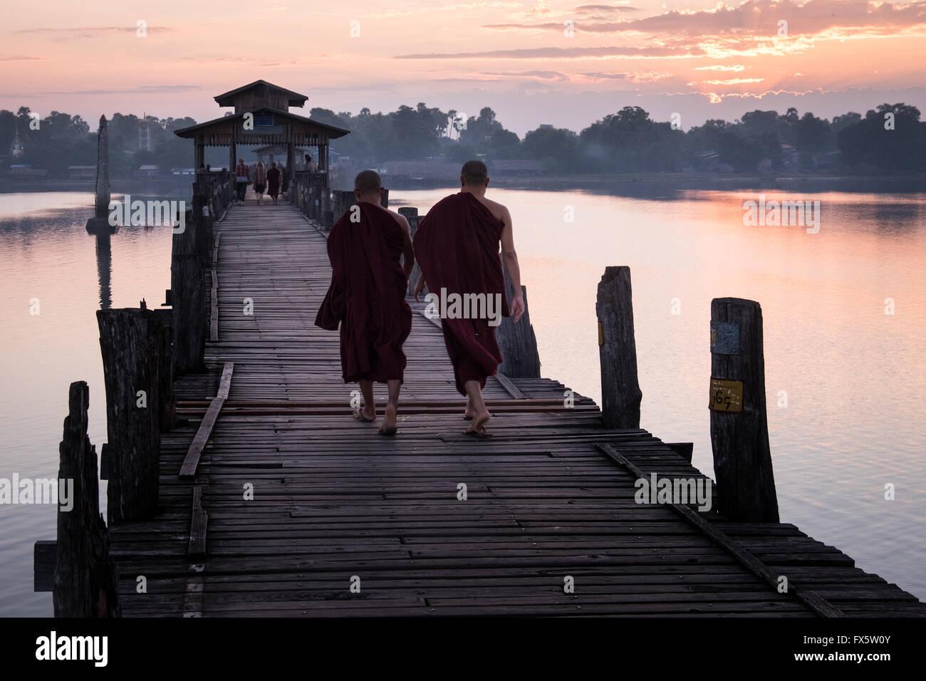 Two monks walk across the wooden U Bein's Bridge near Amapura in Mandalay. Stock Photo