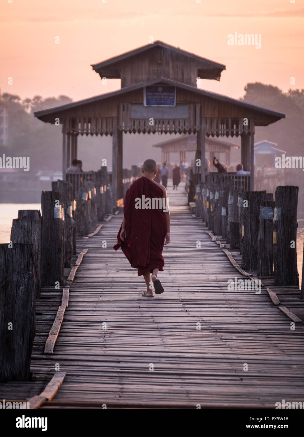 A Novice walking across U Bein's Bridge at dawn - Stock Image