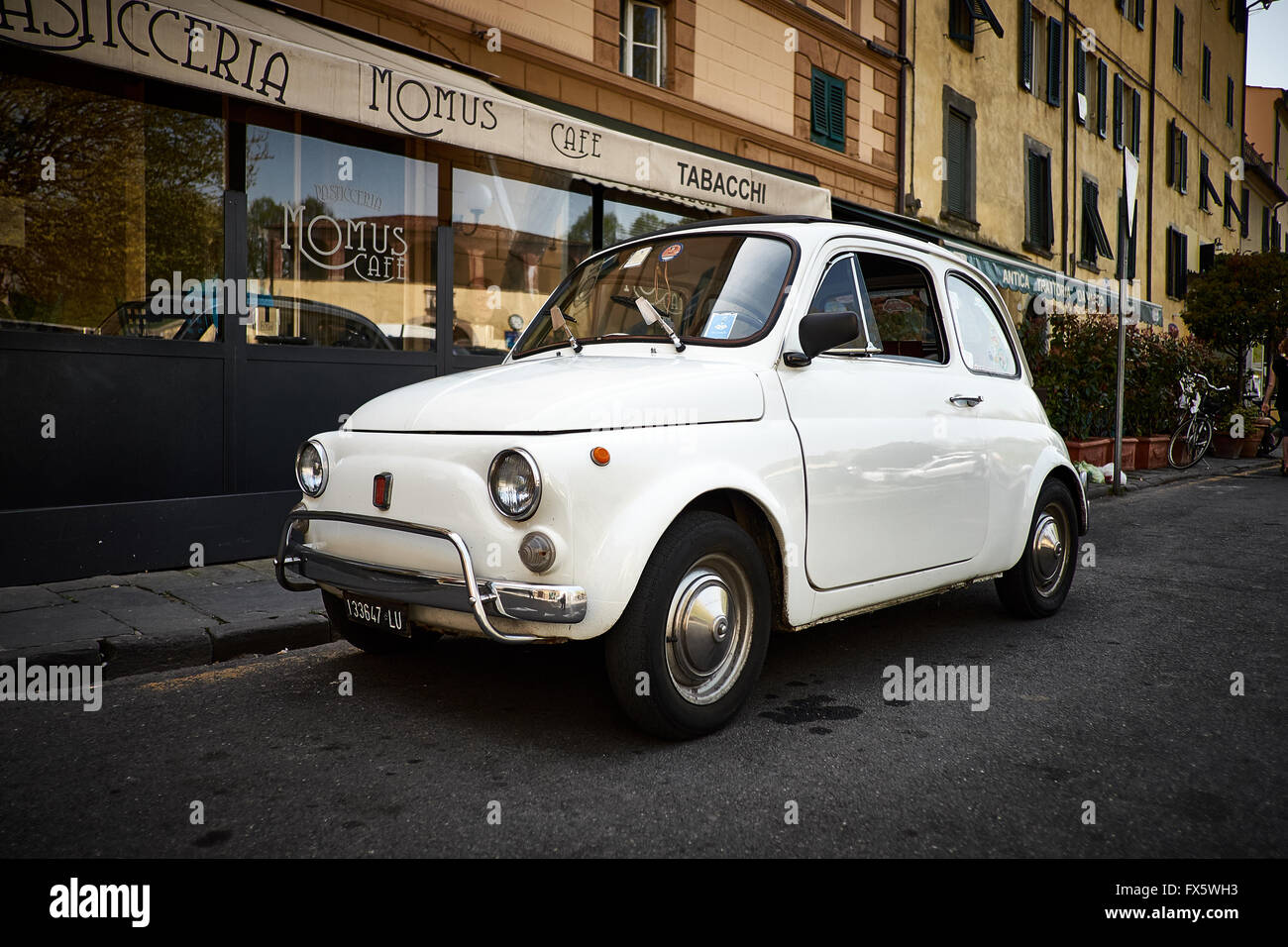 A Classic white Fiat 500 L Lusso (1968 - 1972) car parked in front of an Italian cafe, Tabacci and Pasticceria - Stock Image