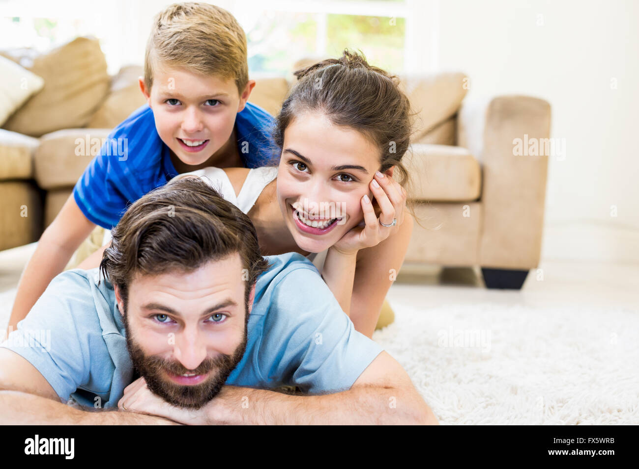 Portrait of parents and son lying on rug - Stock Image