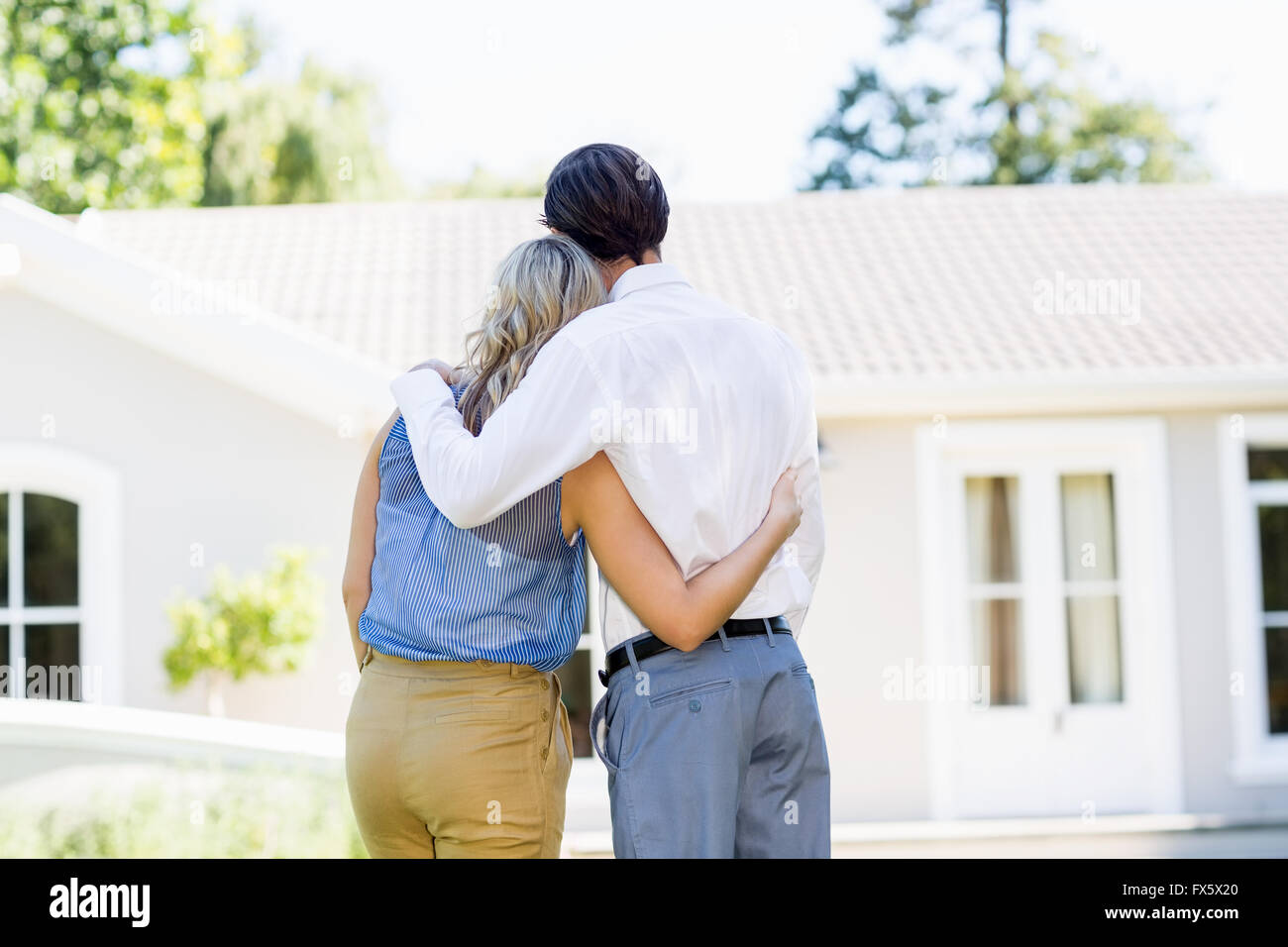 Rear view of couple standing with arm around - Stock Image