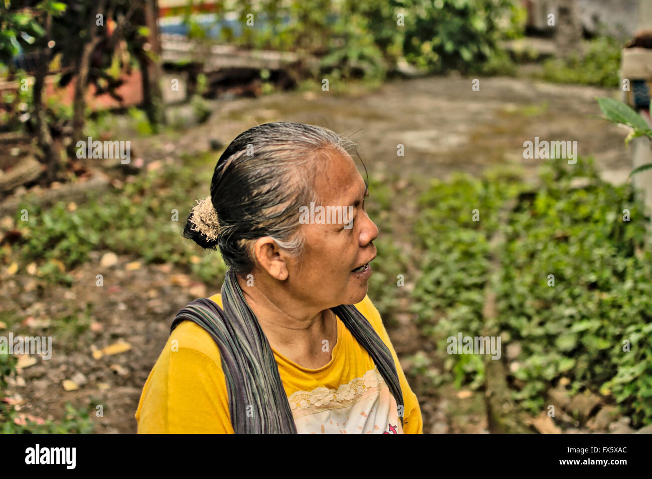 A Javanese woman seller of jamu, traditional Indonesian medicine, which she makes herself from herbs. - Stock Image