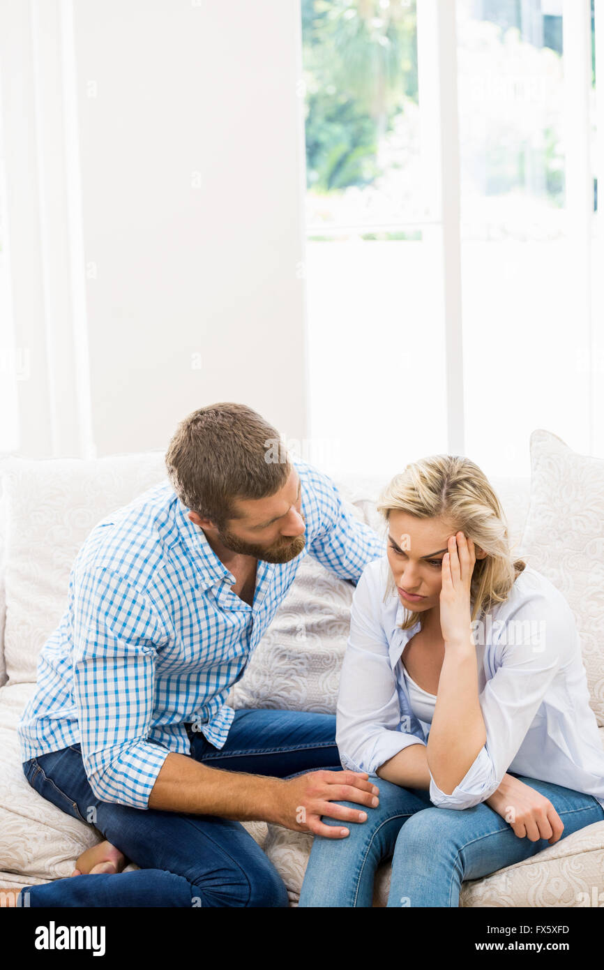 Man comforting her woman in living room - Stock Image