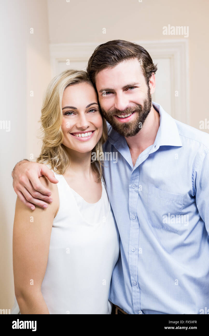 Happy couple standing with arm around - Stock Image