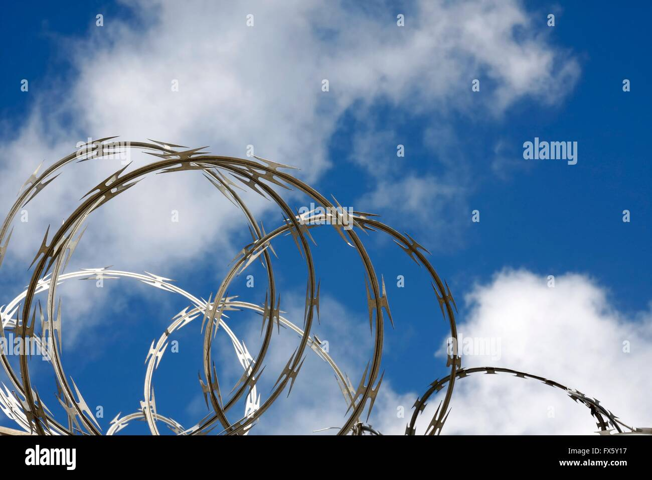 Razor wire against a blue sky with clouds Stock Photo