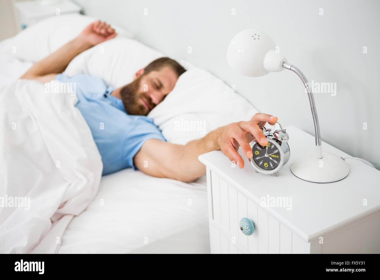 Sleeping man awakened by a alarm on bed - Stock Image