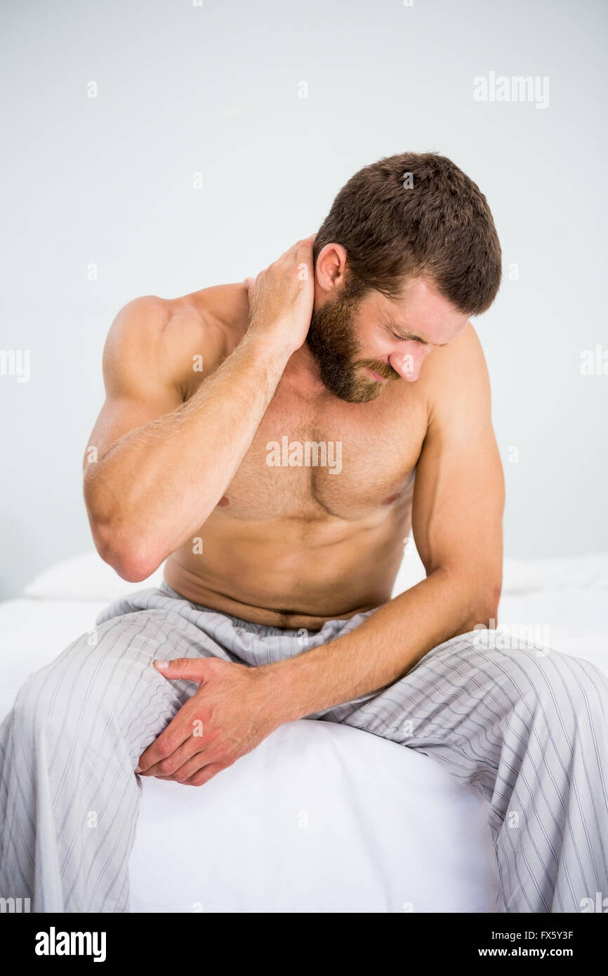 Man suffering from neck ache on bed - Stock Image