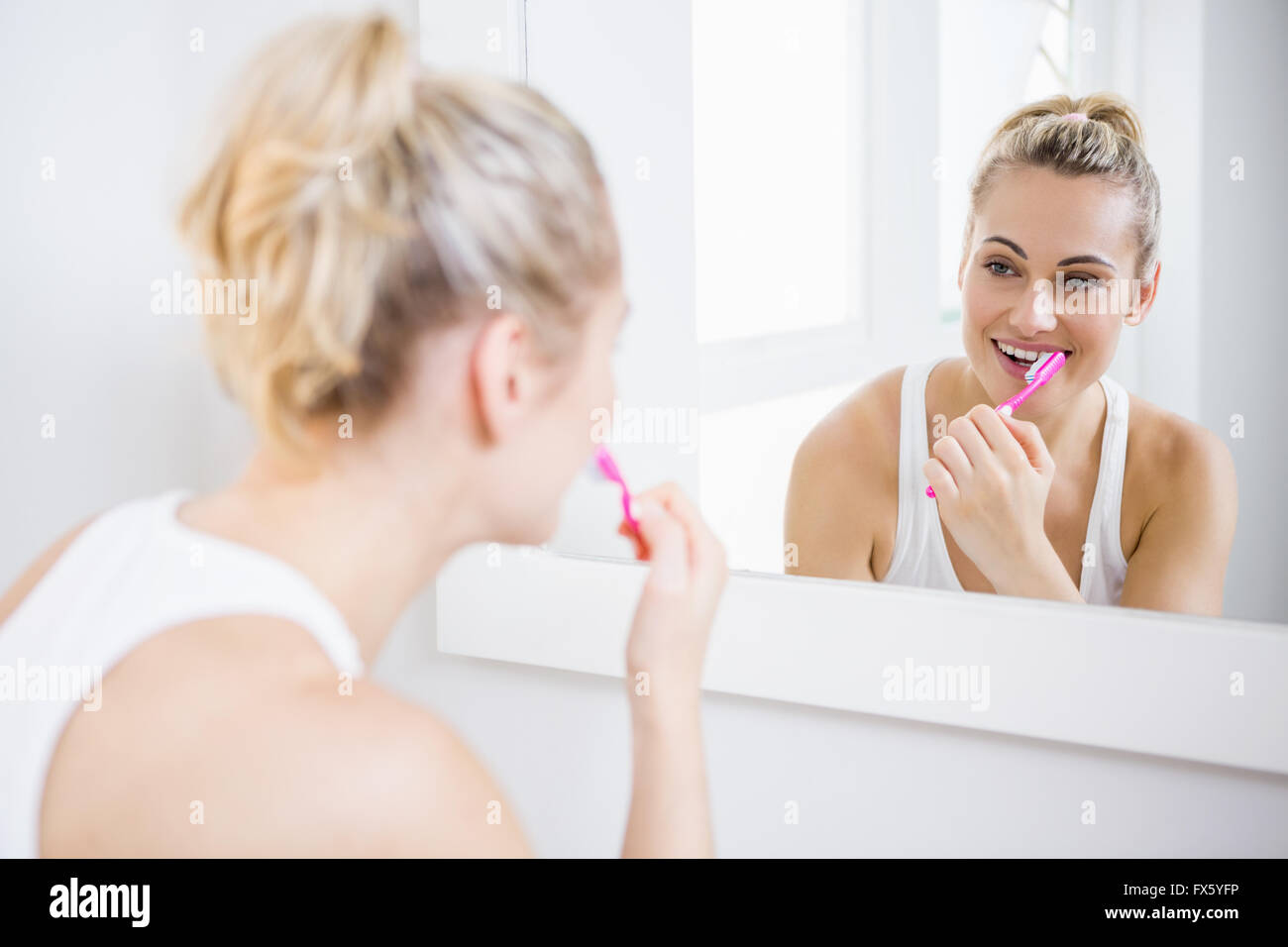 Young woman brushing teeth in bathroom - Stock Image