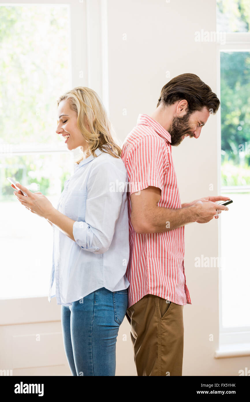 Couple standing back to back and text messing on mobile phone - Stock Image