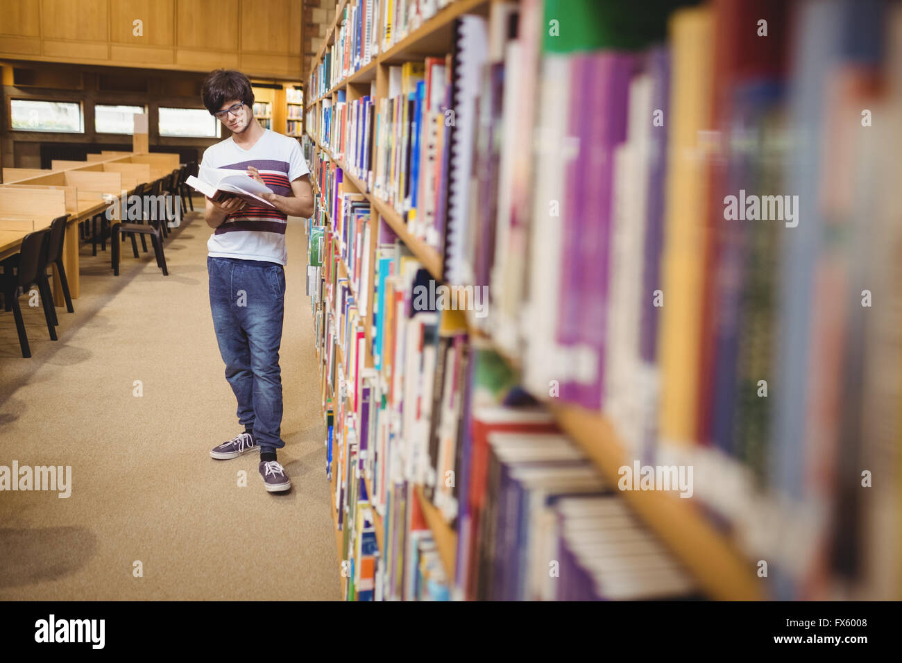 Young student reading book while standing near bookshelf - Stock Image