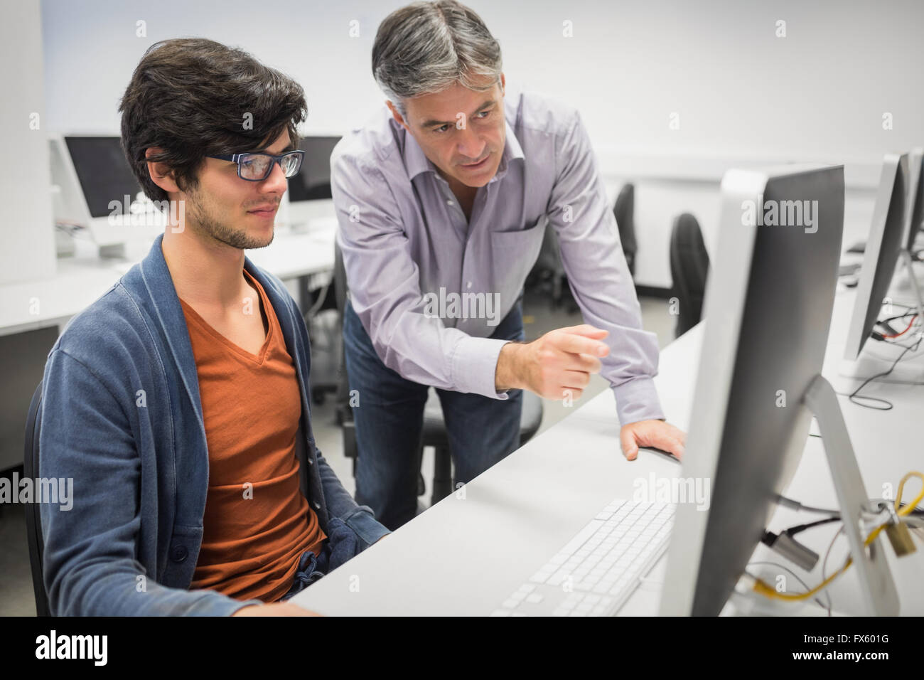 Computer teacher assisting a student - Stock Image