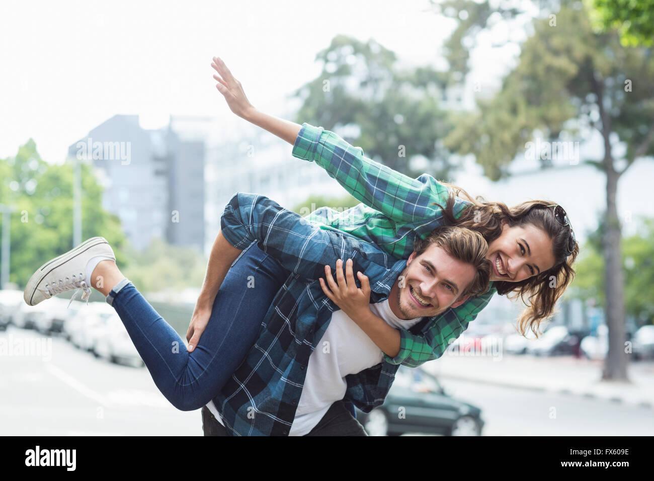 Man giving piggyback to woman - Stock Image